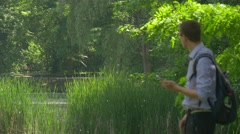Man With Smartphone Comes Texting Summer Park Holding a Mobile Phone and - stock footage