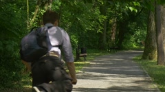 Male Backpacker Gets on a Bicycle Riding a Bike Away in Park Alley Bench Under - stock footage