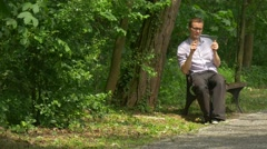 Man Clicks Tablet in Green Park Gets up of Bench Walking Chatting Forex Real - stock footage