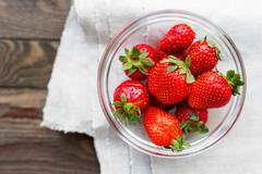 Fresh juicy strawberries in glass bowl. Rustic background with homespun napki Stock Photos