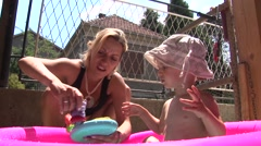 Mom and her daughter playing in a small pool Stock Footage