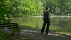 Man Resting in Park Standing at the Bench by Lake Tourist in Park Fresh Green Stock Footage