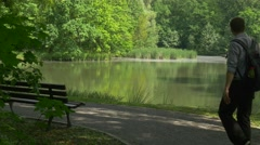 Backpacker Comes Sits Down Resting on a Bench Sunny Summer Day by the Lake Stock Footage