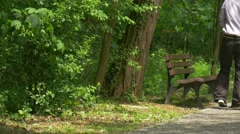 Man Sits on a Bench Holding a Tablet in Park Thinking Looking at the Trees - stock footage