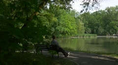 Man is Sitting on the Bench in Park Alley Sunny Day by the Lake Fresh Green Stock Footage