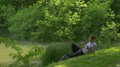 Businessman With Mobile Phone Sitting on Green Hill Holding a Smartphone Spends Stock Footage