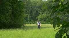Man With Smartphone Walking by High Grass Green Park Man Holding a Phone Typing Stock Footage