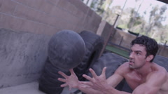 Tracking the medicine ball as it is thrown by a man while he is exercising Stock Footage