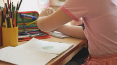 Little girls draw a pictures in the copybook Stock Footage