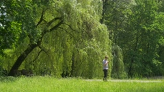 Man Talking by Smartphone Walking by Park Alley Green Trees Willows Grow Along - stock footage