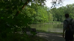 Man Sits Down to the Bench in Park Alley Sunny Day by the Lake Fresh Green Stock Footage