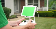 Hobbyist Uses Remote Control for Drone Outside a House Green Screen Tablet Stock Footage