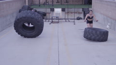 A woman and a man doing tire lifts as a fitness / crossfit exercise Arkistovideo