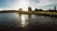 A Man on a SUP Stand Up Paddle Board Near Gas Works Park in Seattle at Sunset - stock footage