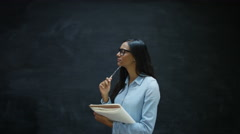 4K Smiling woman writing in notebook on chalkboard background Stock Footage