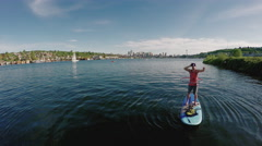SUP Man Stand Up Paddleboarding While Spinning a Hula Hoop in Seattle Lake Union Stock Footage