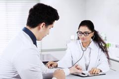 Doctor checking patient's heartbeat - stock photo