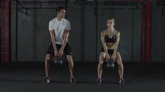 A man and woman doing kettle bell exercising and lifts, squats Stock Footage