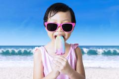 Female child eats ice cream at shore - stock photo