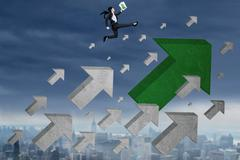 Female worker with arrow sign jumps at sky - stock photo