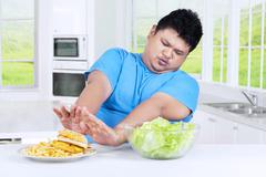 Man avoid a plate of junk food Stock Photos