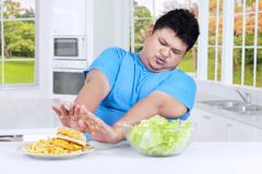Man refuses fast food in the kitchen - stock photo