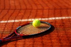 Tennis ball and racket on the court. Orange color background - stock photo