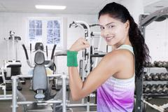 Woman showing bicep at gym in winter season Stock Photos