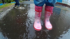 Child in boots walking and jumping in muddy puddle after rain. Stock Footage