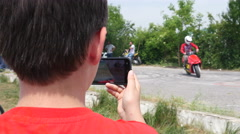 Spectator boy holding shooting video via smart phone of a show daytime Stock Footage
