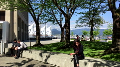 People resting and reading mobile message in downtown Vancouver BC Canada. Stock Footage