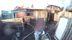 Fire. Firefighter extinguishes the roof of the burning building from the ground. Stock Footage