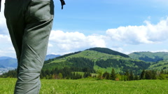 4K . Adult man  tourist go  on mountain hill in sunny day. Backpacker team Stock Footage