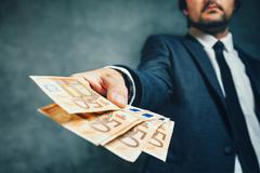 Businessman from bank offering money loan in euro banknotes Stock Photos