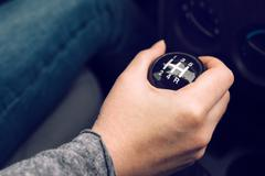 Female driver hand shifting gear manually - stock photo