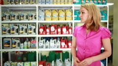 Seller in the store helps girl to choose engine oil. Stock Footage