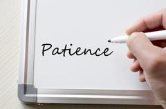 Patience written on whiteboard - stock photo