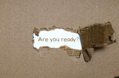 The word are you ready appearing behind torn paper. Stock Photos