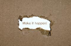 The word make it happen appearing behind torn paper. Stock Photos