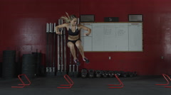 Dolly wide shot of a young woman jumping side to side over mini hurdles Stock Footage