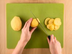 Hands slicing potatoe on green plastic board - stock photo