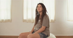 Pregnant woman with dreadlocks sitting on a physio ball  Stock Footage