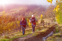 Two Hikers Walking on Rural Trail among Autumnal Forest - stock photo