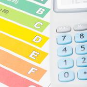 Colorful energy efficiency chart and neat calculator over it Stock Photos