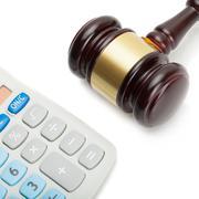 Wooden judge's gavel next to neat calculator Stock Photos