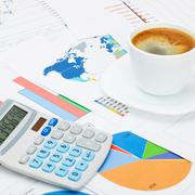 Coffee cup and calculator over world map and financial charts Kuvituskuvat