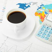Coffee cup and calculator over world map and some financial charts Kuvituskuvat
