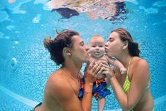 Baby with parents learn to swim underwater in swimming pool - stock photo