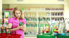 Man seller in the store helps girl to choose engine oil. calling on the phone Stock Footage