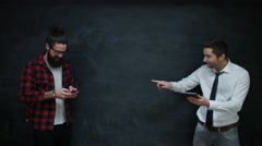 4K Happy casual businessmen using interactive technology together on chalkboard Arkistovideo